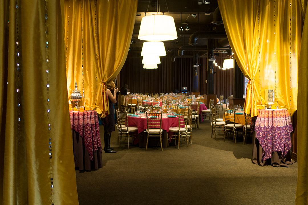 Caravale event photo showing Palace Ballroom decorated with mosaic table cloths, golden drapes, and flowers